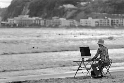 海辺でPCを使う男性